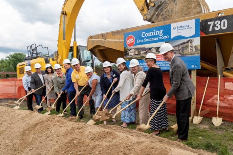 A construction site with several people holding shovels, ready to break ground.