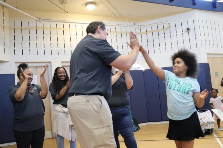 Sean Auton, an HMB attorney, gives a young girl a high five in a gymnasium.